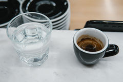 Cup with coffee near a glass of water Stock Image