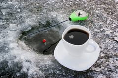 Cup of coffee near ice hole with float Royalty Free Stock Photo