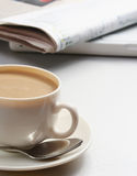 Cup of coffee near newspapers Stock Image