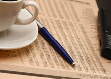 Cup of coffee near press and pen Stock Photos