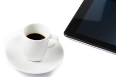 Cup of coffee near a tablet, concept of new technology Stock Image