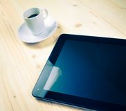 Cup of coffee near a tablet, concept of new technology Stock Photo