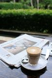 Cup of coffee with news paper on table. Cup of fresh coffee on a table ready for drinking royalty free stock photo