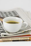 Cup of coffee on newspaper Stock Photos