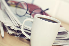 Cup of coffee and newspaper on table Stock Photo