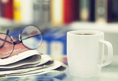 Cup of coffee and newspaper on table Royalty Free Stock Photo