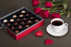 A cup of coffee next to a box of chocolate and red roses. Dark and light chocolate candy in a red and silver box next to red roses and coffee in a white cup and stock photo