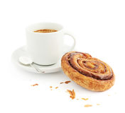 Cup of coffee next to cinnamon bun Royalty Free Stock Image