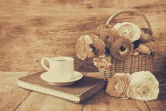 Cup of coffee next to old book next to flowers on wooden table Stock Photography