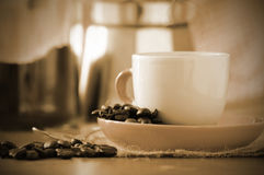 Cup of coffee next to some coffee beans on a table in a rustic kitchen. Empty copy space for editor's text Royalty Free Stock Photos