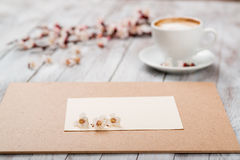A cup of coffee next to the spring white flowers on wooden texture. Space for text. Royalty Free Stock Photos