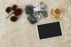 Cup of coffee next to tablet device with empty screen over cozy and warm fur carpet. Top view. Royalty Free Stock Photography