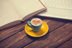 Cup of coffee and notbook. Cup of coffee with heart shape and notbook on wooden table Royalty Free Stock Photos