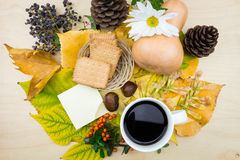 A cup of coffee and note with bouquet of autumn leaves,berries and seeds. Royalty Free Stock Images