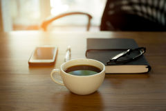 Cup of coffee and note pad with pen and glasses on the wooden de. Sk with sunlight Royalty Free Stock Photo