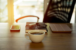 Cup of coffee and note pad with pen and glasses on the wooden de. Sk with sunlight Royalty Free Stock Images