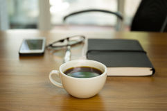 Cup of coffee and note pad with pen and glasses. On the wooden desk Stock Image