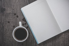 Cup of coffee and note. Cup of coffee on the wooden background with a note Stock Photography