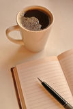 A cup of coffee with notebook and  black  pen in sunrise light Stock Photos