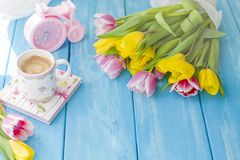 A cup of coffee on a notebook on a blue wooden background. Bright colors. Bouquet of flowers yellow and pink. The pink clock is stock photography