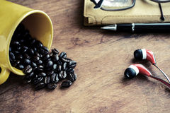 Cup of coffee and notebook with coffee bean on old wooden table Royalty Free Stock Photo