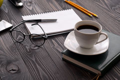 Cup of coffee with notebook and glasses Stock Images