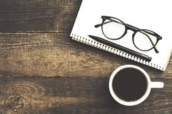 Cup of coffee, notebook, glasses and pen stock photo