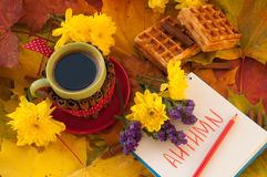 A cup of coffee, a notebook, homemade waffles, maple leaves, autumn flowers and cinnamon sticks Royalty Free Stock Images