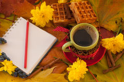 A cup of coffee, a notebook, homemade waffles, maple leaves, autumn flowers and cinnamon sticks Royalty Free Stock Photography
