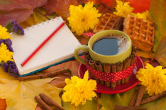 A cup of coffee, a notebook, homemade waffles, maple leaves, autumn flowers and cinnamon sticks Royalty Free Stock Photo