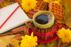 A cup of coffee, a notebook, homemade waffles, maple leaves, autumn flowers and cinnamon sticks Stock Images