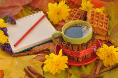 A cup of coffee, a notebook, homemade waffles, maple leaves, autumn flowers and cinnamon sticks Royalty Free Stock Image