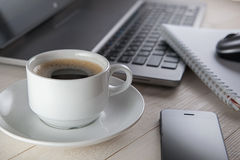 Cup of coffee and notebook, laptop, computer mouse, phone on a t Stock Image