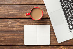 Cup of coffee and notebook with laptop computer Royalty Free Stock Photo