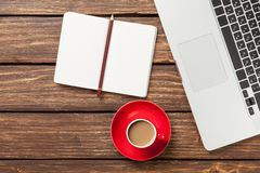 Cup of coffee and notebook with laptop computer Stock Image