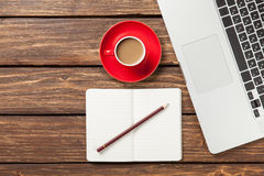 Cup of coffee and notebook with laptop computer Royalty Free Stock Image