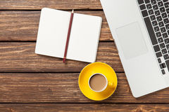 Cup of coffee and notebook with laptop computer Stock Photos