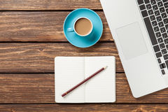 Cup of coffee and notebook with laptop computer Stock Images