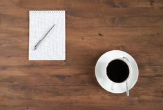 Cup of coffee and notebook on old  table Stock Photography