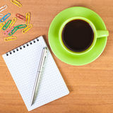 A cup of coffee with a notebook and pen Royalty Free Stock Images