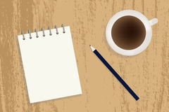 A cup of coffee, notebook and pencil on a table Royalty Free Stock Photography