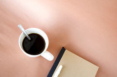 Cup of coffee with notebook on pink Royalty Free Stock Image