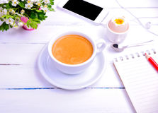 Cup of coffee and notebook with a red pencil Royalty Free Stock Image
