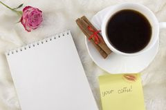 A cup of coffee, a notebook, a sticker of your coffee, a rose, on a white background decoration royalty free stock images