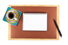 Cup of coffee and a notebook on textured paper Royalty Free Stock Images