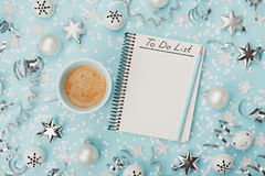 Cup of coffee and notebook with to do list on blue background top view.  Christmas planning concept. Flat lay. Stock Image