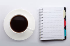 A cup of coffee and a notebook. On white background Royalty Free Stock Photo