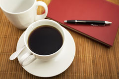 A cup of coffee and a notebook. On wood Stock Images