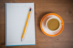 Cup of coffee and notebook on wooden. Royalty Free Stock Photo