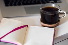 A cup of coffee and a notebook on your desktop royalty free stock image